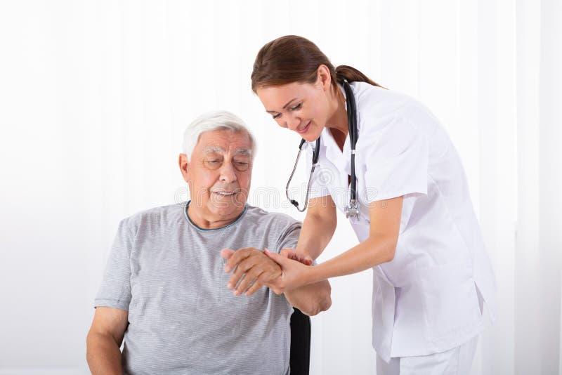 Γιατρός που εξετάζει το σφυγμό του αρσενικού ασθενή στοκ εικόνα με δικαίωμα ελεύθερης χρήσης