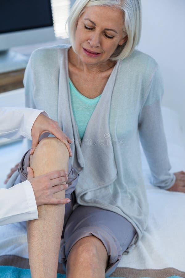 Γιατρός που εξετάζει το υπομονετικό γόνατο στοκ εικόνες