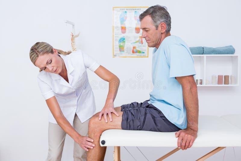 Γιατρός που εξετάζει το υπομονετικό γόνατό της στοκ εικόνες