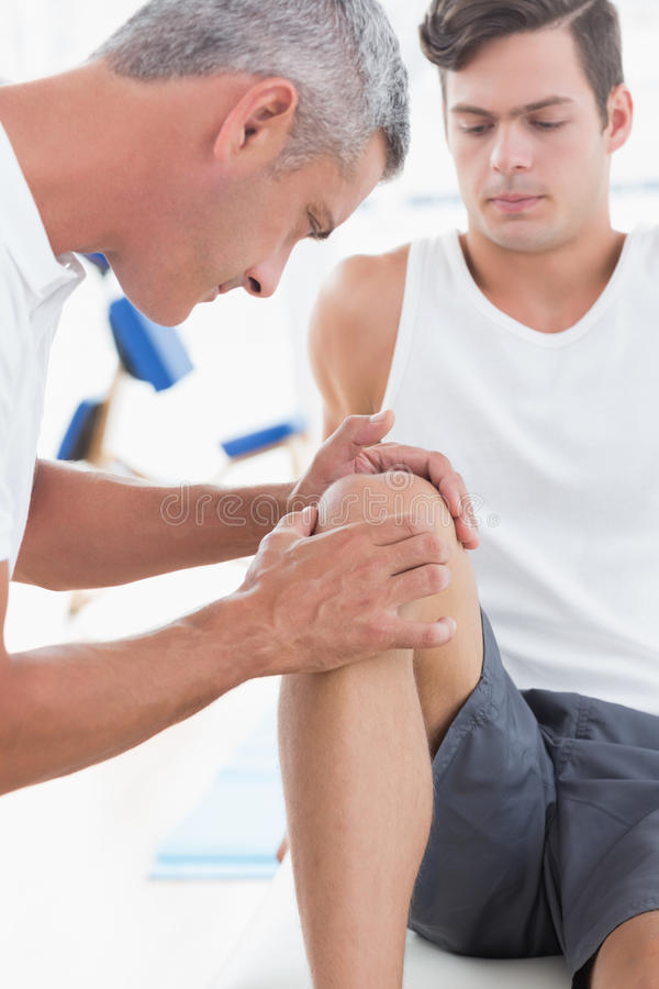 Γιατρός που εξετάζει το υπομονετικό γόνατό του στοκ φωτογραφίες