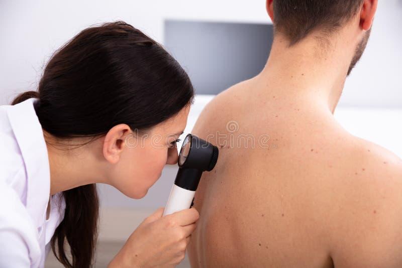 Γιατρός που εξετάζει το χρωματισμένο δέρμα στην ανθρώπινη πλάτη στοκ φωτογραφία με δικαίωμα ελεύθερης χρήσης