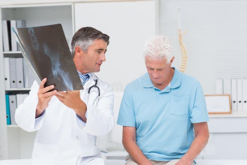 Γιατρός που εξηγεί την ακτίνα X εξετάζοντας το λυπημένο ανώτερο ασθενή στοκ εικόνες