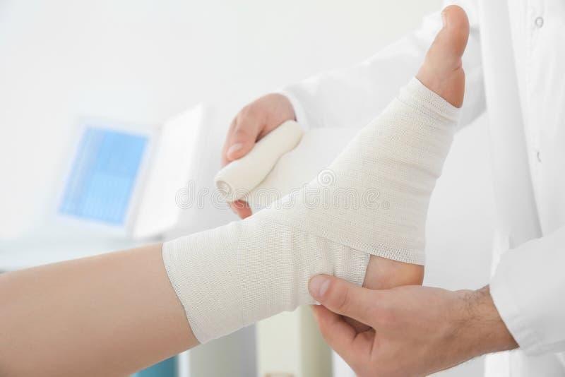 Γιατρός που εφαρμόζει τον επίδεσμο επάνω στο υπομονετικό πόδι ` s στην κλινική, στοκ εικόνες με δικαίωμα ελεύθερης χρήσης