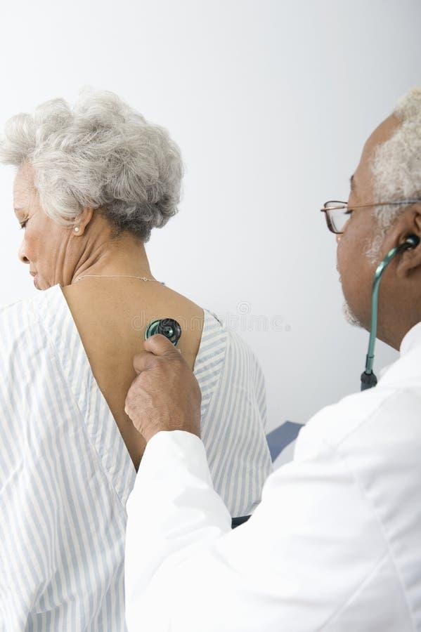 Γιατρός που ελέγχει την πλάτη του ασθενή που χρησιμοποιεί ένα στηθοσκόπιο στοκ εικόνες