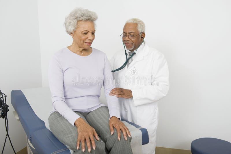 Γιατρός που ελέγχει την πλάτη του ασθενή που χρησιμοποιεί το στηθοσκόπιο στοκ εικόνες με δικαίωμα ελεύθερης χρήσης