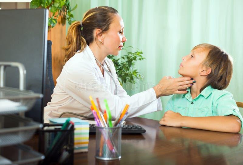 Γιατρός που ελέγχει το θυροειδή του εφήβου στοκ εικόνες