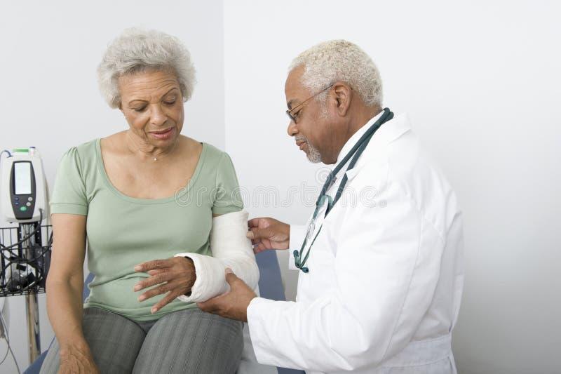 Γιατρός που ελέγχει το σπασμένο χέρι του ασθενή στοκ φωτογραφίες