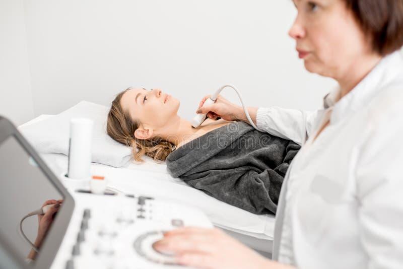 Γιατρός που κάνει την εξέταση υπερήχου σε μια νέα γυναίκα στοκ εικόνα με δικαίωμα ελεύθερης χρήσης