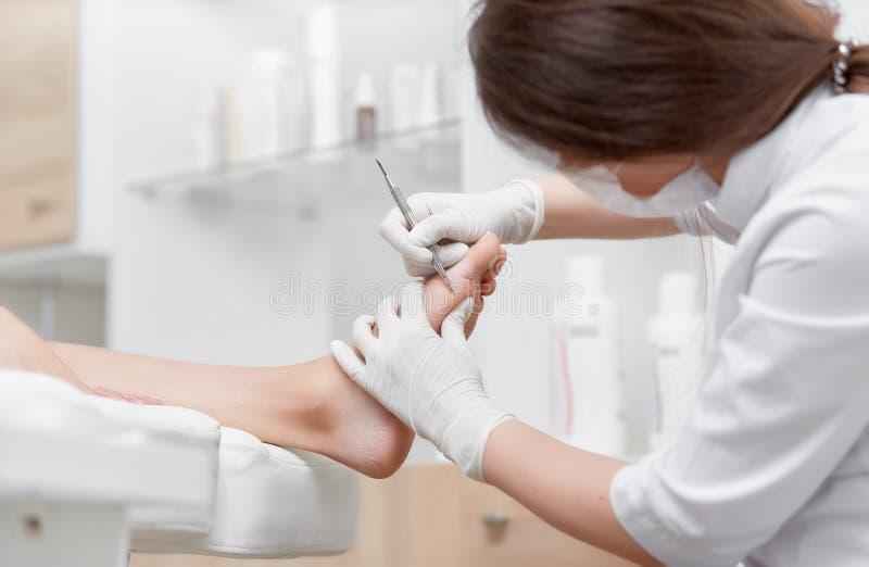 Γιατρός που κάνει το πόδι πελατών καθαρίζοντας διαδικασίας με το ειδικό εργαλείο σιδήρου στοκ φωτογραφίες με δικαίωμα ελεύθερης χρήσης