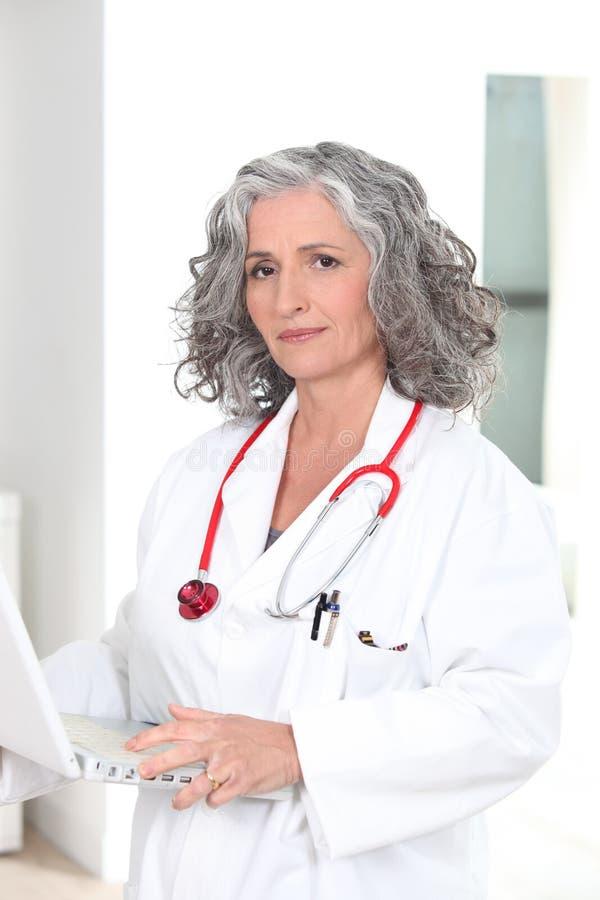 Γιατρός που κρατά ένα lap-top στοκ εικόνα με δικαίωμα ελεύθερης χρήσης