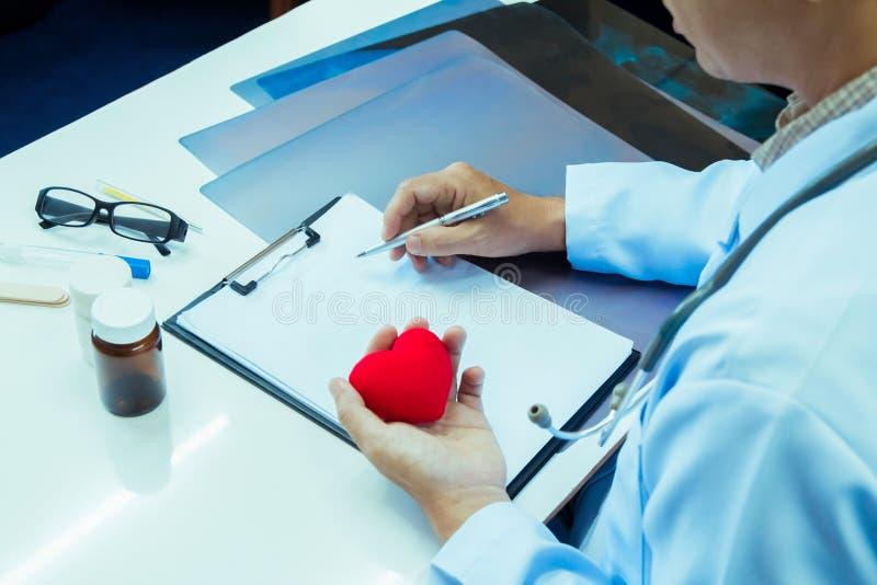 Γιατρός που κρατά το κόκκινο σχέδιο επεξεργασίας εκθέσεων γραψίματος καρδιών και μανδρών για το γραφείο στοκ φωτογραφίες με δικαίωμα ελεύθερης χρήσης