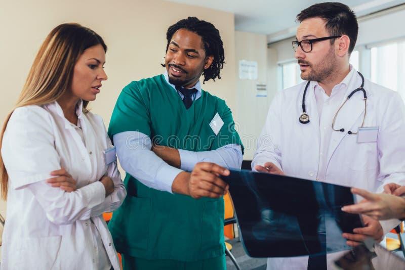 Γιατρός που κρατά ψηλά μια ακτίνα X με τους συντροφικούς γιατρούς στοκ φωτογραφία με δικαίωμα ελεύθερης χρήσης
