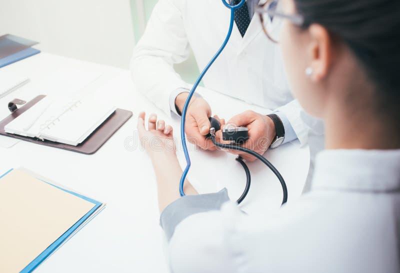 Γιατρός που μετρά την πίεση στοκ φωτογραφία με δικαίωμα ελεύθερης χρήσης