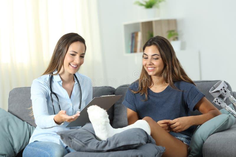 Γιατρός που μιλά με έναν με ειδικές ανάγκες εξωτερικό ασθενή στο σπίτι στοκ φωτογραφία με δικαίωμα ελεύθερης χρήσης