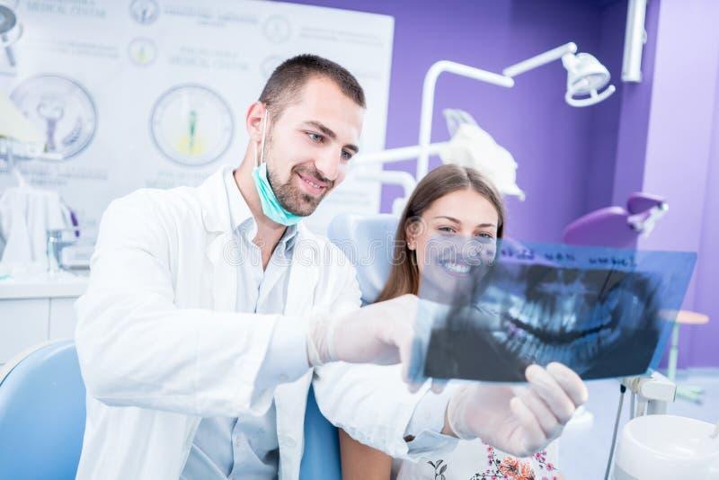Γιατρός που μιλά με υπομονετικό και που παρουσιάζει μια ακτηνογραφία στο stomatol στοκ φωτογραφίες με δικαίωμα ελεύθερης χρήσης
