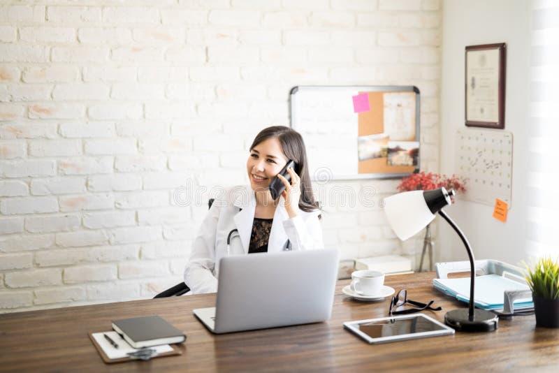 Γιατρός που μιλά στο τηλέφωνο με τον ασθενή στοκ φωτογραφίες