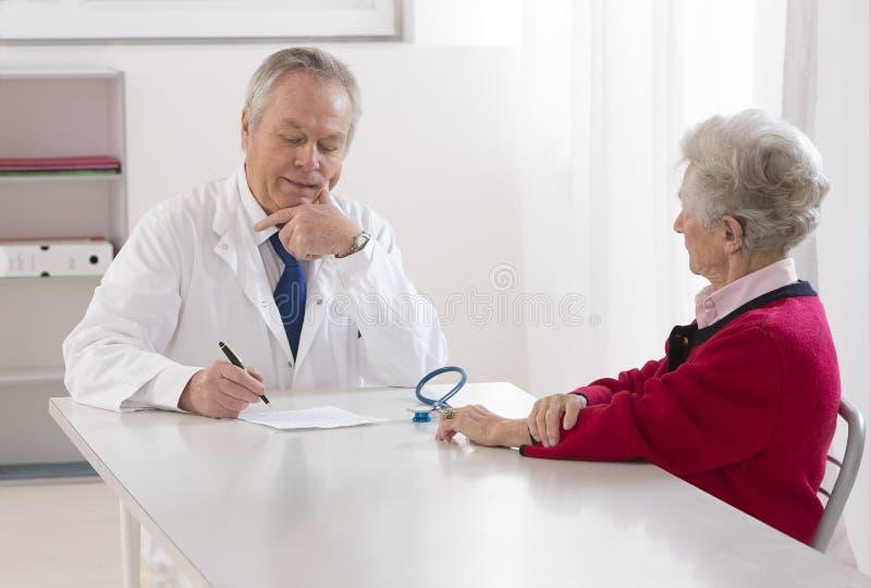 Γιατρός που μιλά στο θηλυκό ανώτερο ασθενή του στοκ εικόνα με δικαίωμα ελεύθερης χρήσης