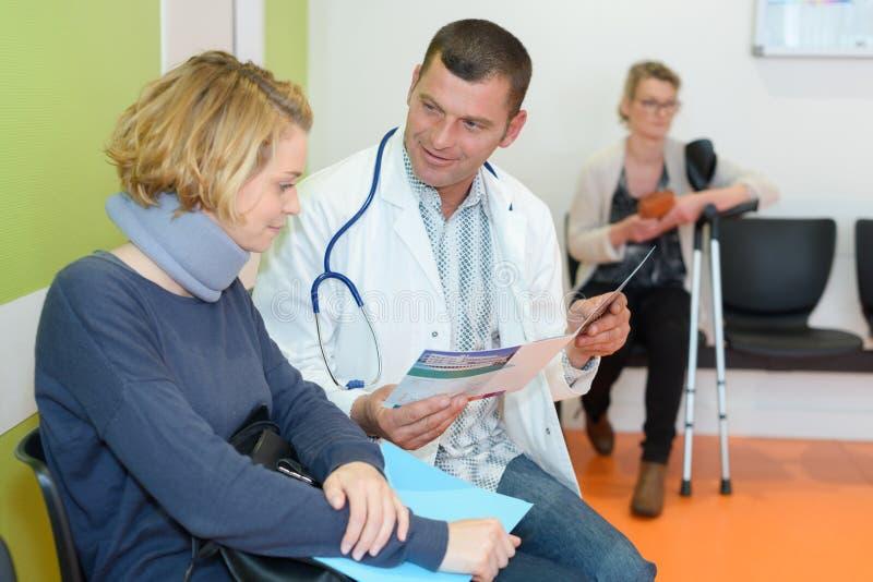 Γιατρός που μιλά στο υπομονετικό φορώντας αυχενικός-περιλαίμιο στοκ εικόνες