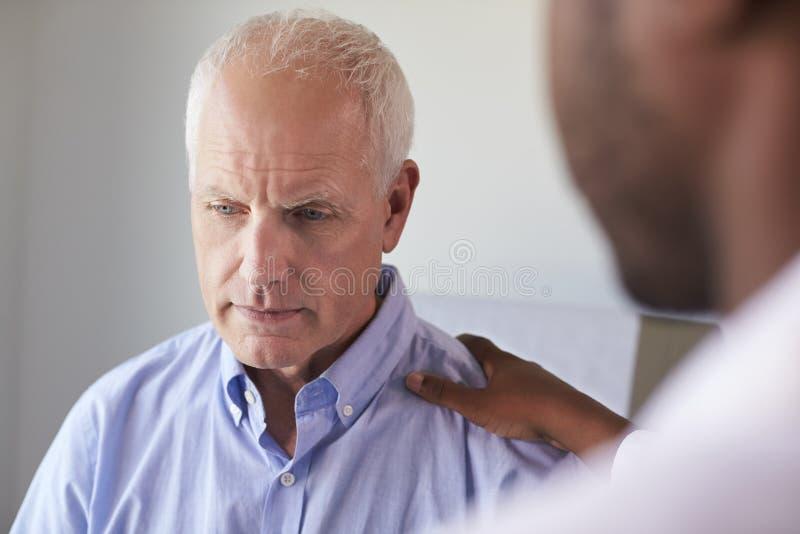 Γιατρός που μιλά στο δυστυχισμένο αρσενικό ασθενή στο δωμάτιο διαγωνισμών στοκ φωτογραφία με δικαίωμα ελεύθερης χρήσης