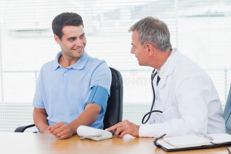 Γιατρός που παίρνει τη πίεση του αίματος του χαμογελώντας ασθενή στοκ φωτογραφία με δικαίωμα ελεύθερης χρήσης
