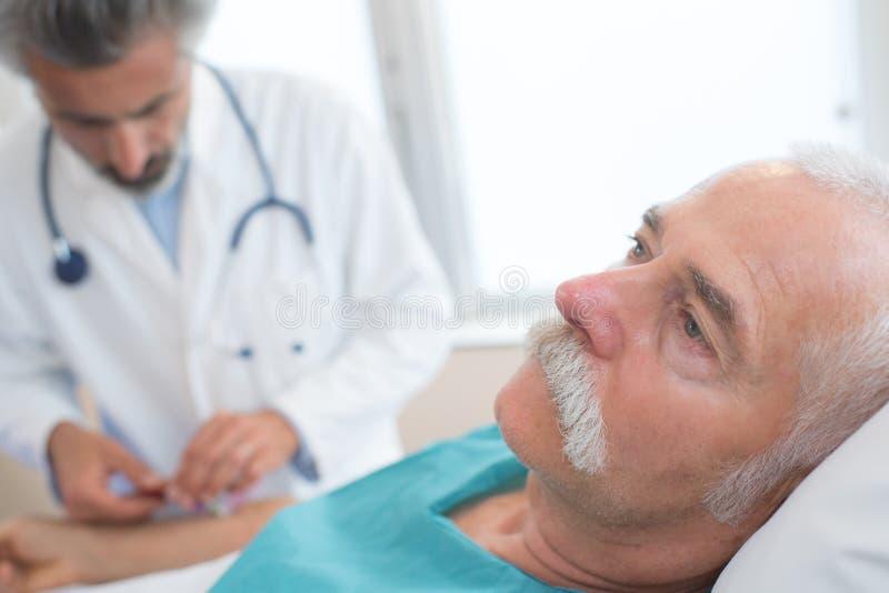 Γιατρός που παίρνει τον αρσενικό ασθενή πίεσης του αίματος στο νοσοκομείο στοκ εικόνα