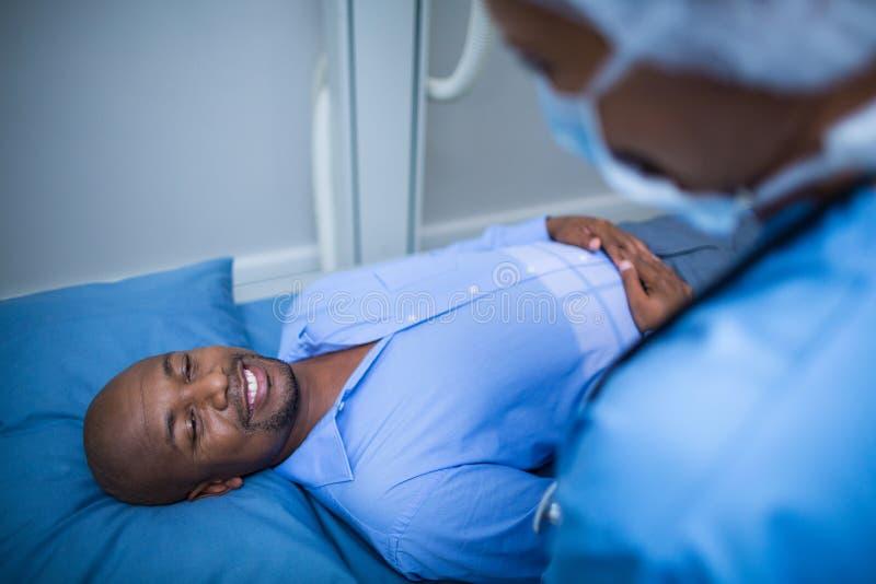 Γιατρός που παρηγορεί έναν ασθενή στο κρεβάτι στοκ εικόνες