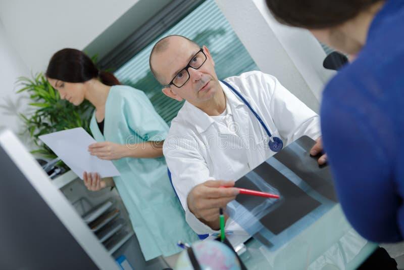 Γιατρός που παρουσιάζει ακτίνα X στον ασθενή στο ιατρικό γραφείο στοκ φωτογραφία με δικαίωμα ελεύθερης χρήσης