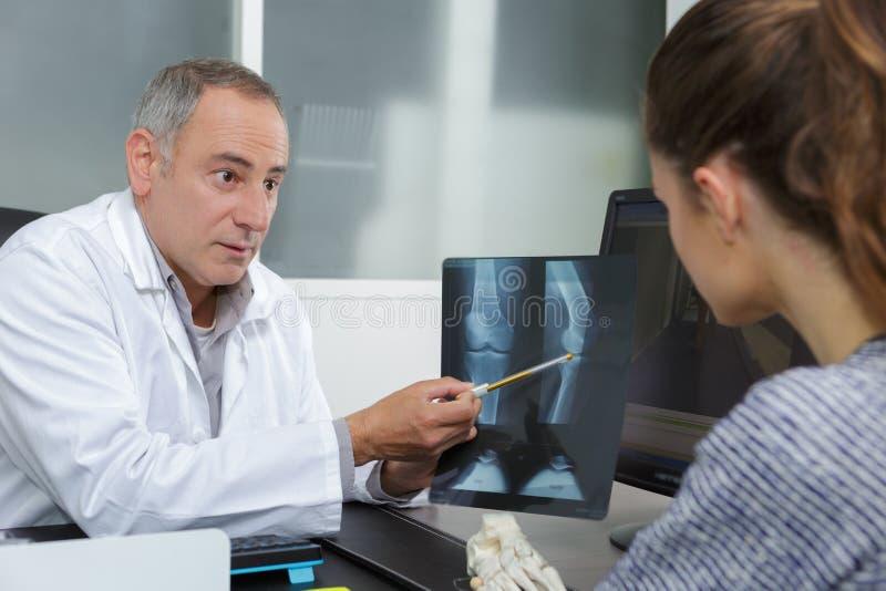 Γιατρός που παρουσιάζει ακτίνες X στον ασθενή στο ιατρικό γραφείο στοκ φωτογραφίες