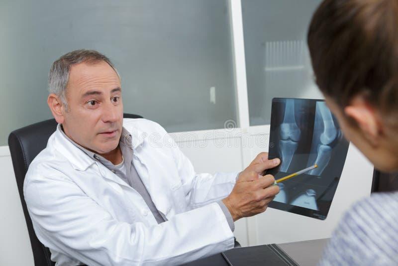 Γιατρός που παρουσιάζει ακτίνες X στον ασθενή στο ιατρικό γραφείο στοκ εικόνες
