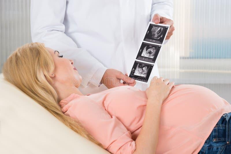 Γιατρός που παρουσιάζει ανίχνευση υπερήχου στη έγκυο γυναίκα στοκ εικόνες