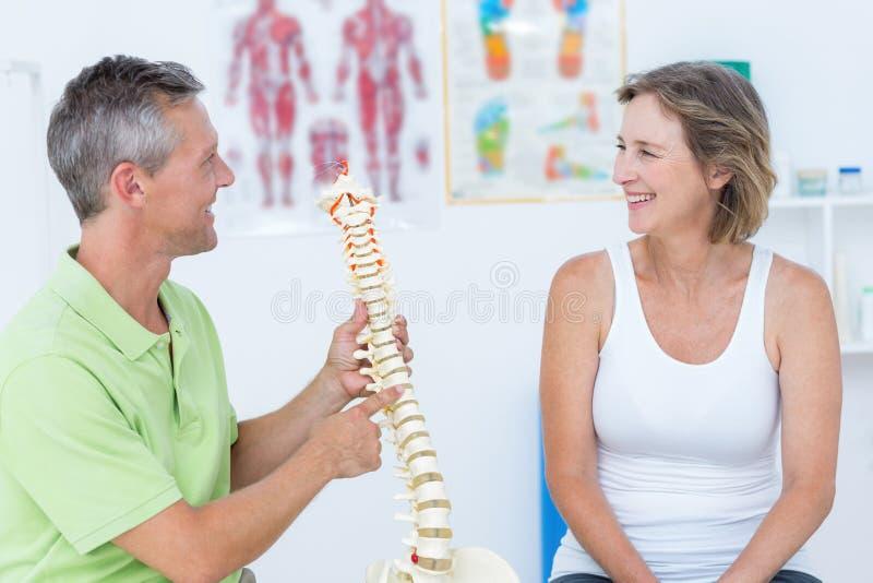 Γιατρός που παρουσιάζει ανατομική σπονδυλική στήλη στοκ εικόνα με δικαίωμα ελεύθερης χρήσης