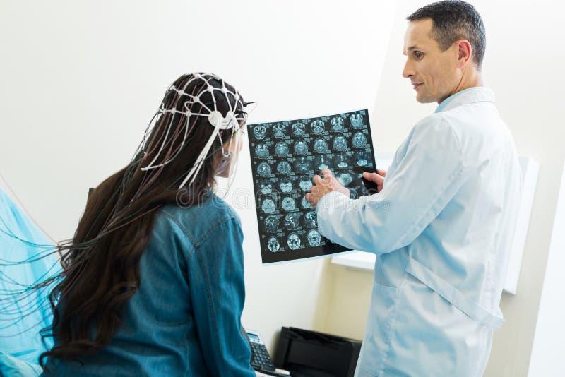 Γιατρός που παρουσιάζει αποτελέσματα ανίχνευσης CT στο υπομονετικό ηλεκτροεγκεφαλογράφημα στοκ εικόνα με δικαίωμα ελεύθερης χρήσης