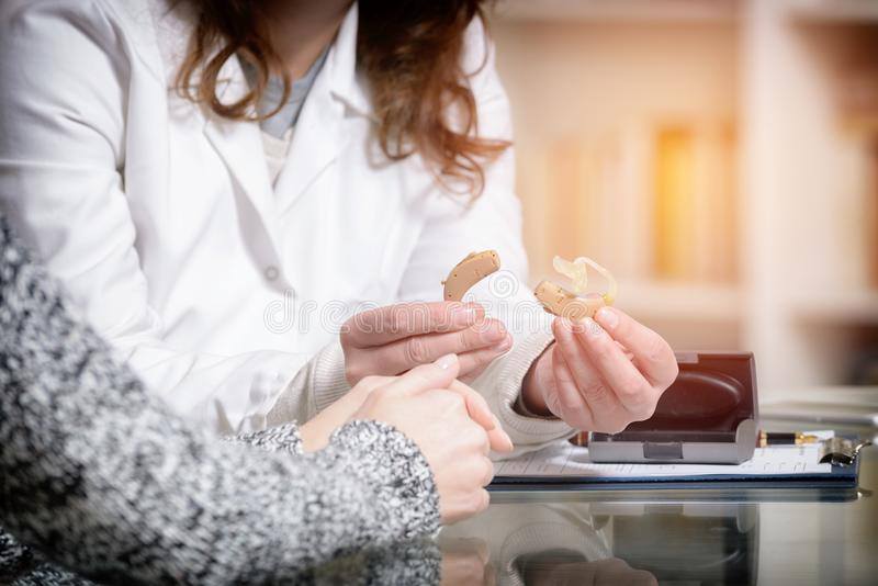 Γιατρός που παρουσιάζει ενίσχυση ακρόασης στοκ εικόνες