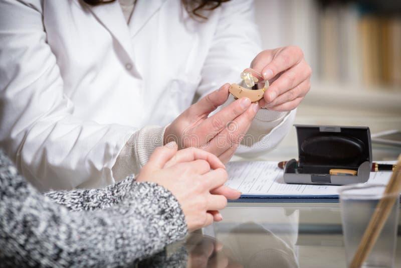 Γιατρός που παρουσιάζει ενίσχυση ακρόασης στοκ φωτογραφία με δικαίωμα ελεύθερης χρήσης