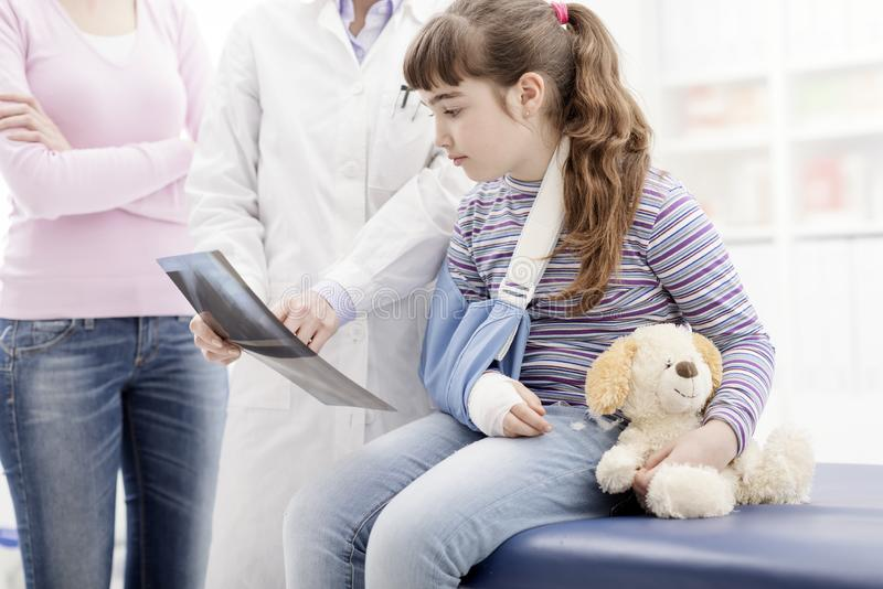 Γιατρός που παρουσιάζει μια ακτίνα X σε έναν νέο ασθενή με το σπασμένο βραχίονα στοκ φωτογραφία