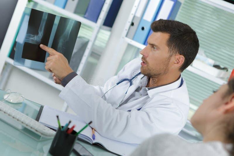 Γιατρός που παρουσιάζει στο υπομονετικό των ακτίνων X αποτέλεσμα στοκ φωτογραφίες