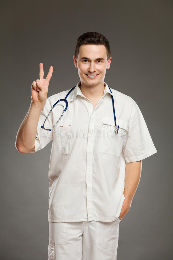 Γιατρός που παρουσιάζει το σημάδι ή αριθμό δύο ειρήνης στοκ εικόνες