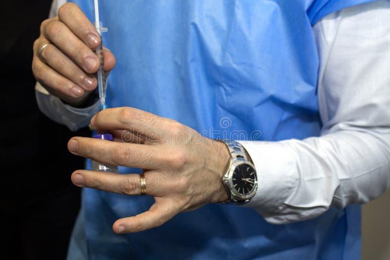 Γιατρός που προετοιμάζει μια σύριγγα με την ιατρική στοκ εικόνες