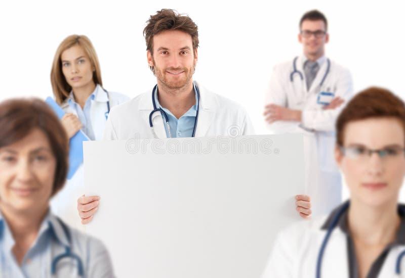 Γιατρός που στέκεται στην ομάδα που κρατά το κενό φύλλο στοκ εικόνα με δικαίωμα ελεύθερης χρήσης