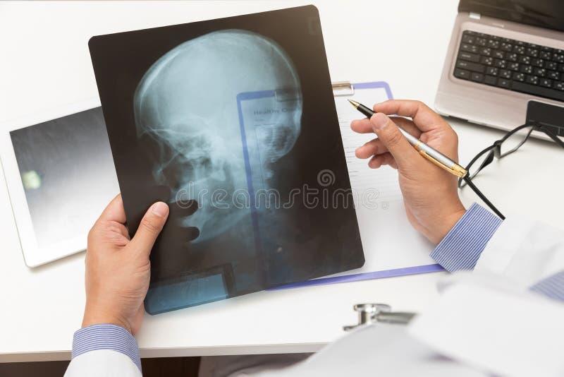 Γιατρός που φαίνεται επικεφαλής των ακτίνων X ταινία στην αρχή στοκ φωτογραφία