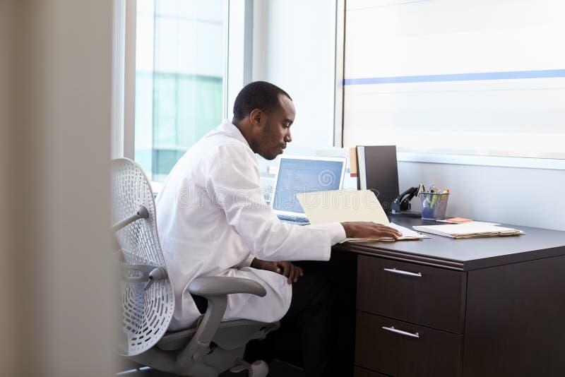Γιατρός που φορά τις άσπρες σημειώσεις ανάγνωσης παλτών στην αρχή στοκ εικόνες