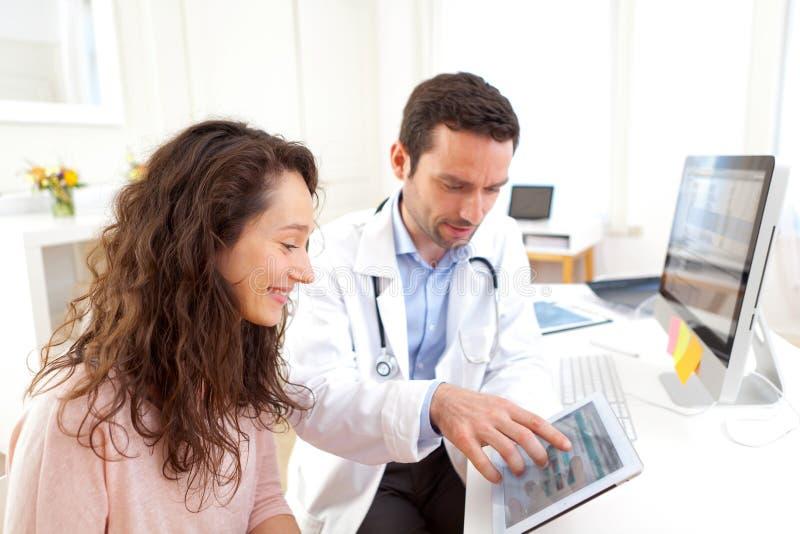 Γιατρός που χρησιμοποιεί την ταμπλέτα για να ενημερώσει τον ασθενή στοκ εικόνες