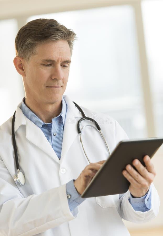 Γιατρός που χρησιμοποιεί την ψηφιακή ταμπλέτα στην κλινική στοκ φωτογραφίες με δικαίωμα ελεύθερης χρήσης