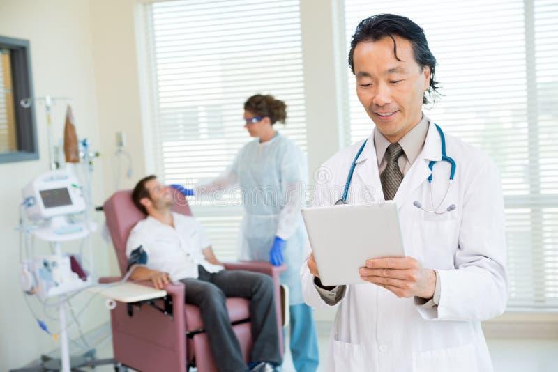 Γιατρός που χρησιμοποιεί την ψηφιακή ταμπλέτα στο δωμάτιο Chemo στοκ εικόνες με δικαίωμα ελεύθερης χρήσης