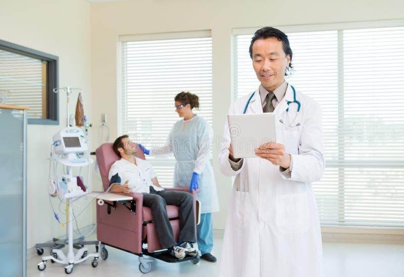 Γιατρός που χρησιμοποιεί την ψηφιακή ταμπλέτα στο δωμάτιο Chemo στοκ φωτογραφίες