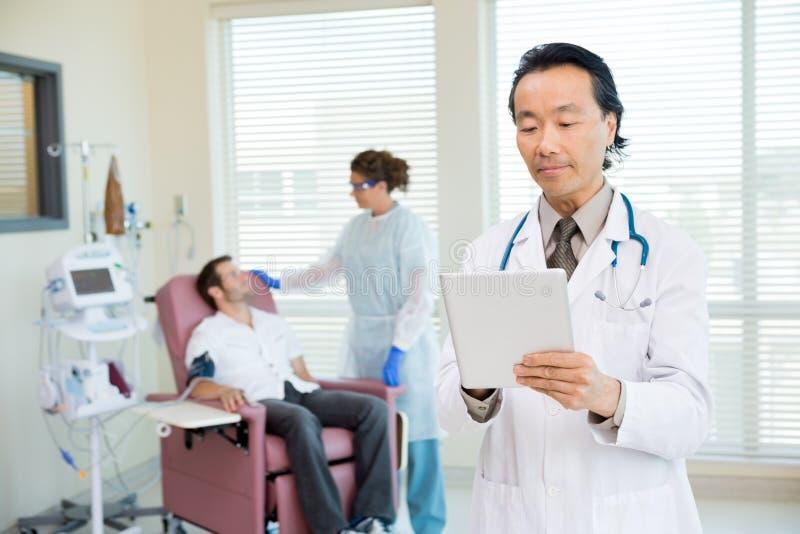 Γιατρός που χρησιμοποιεί την ψηφιακή ταμπλέτα στο δωμάτιο Chemo στοκ φωτογραφία με δικαίωμα ελεύθερης χρήσης