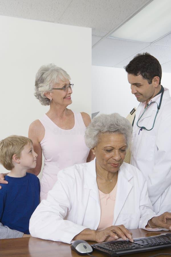 Γιατρός που χρησιμοποιεί το πληκτρολόγιο με τους ασθενείς που συμβουλεύονται το συνάδελφό της στοκ εικόνα