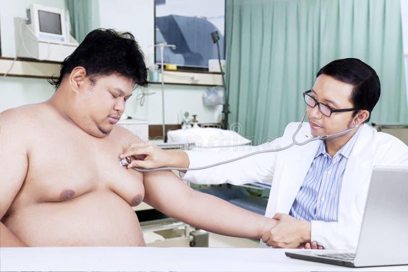Γιατρός που χρησιμοποιεί το στηθοσκόπιο για να ακούσει κτύπος της καρδιάς του ασθενή στοκ φωτογραφίες