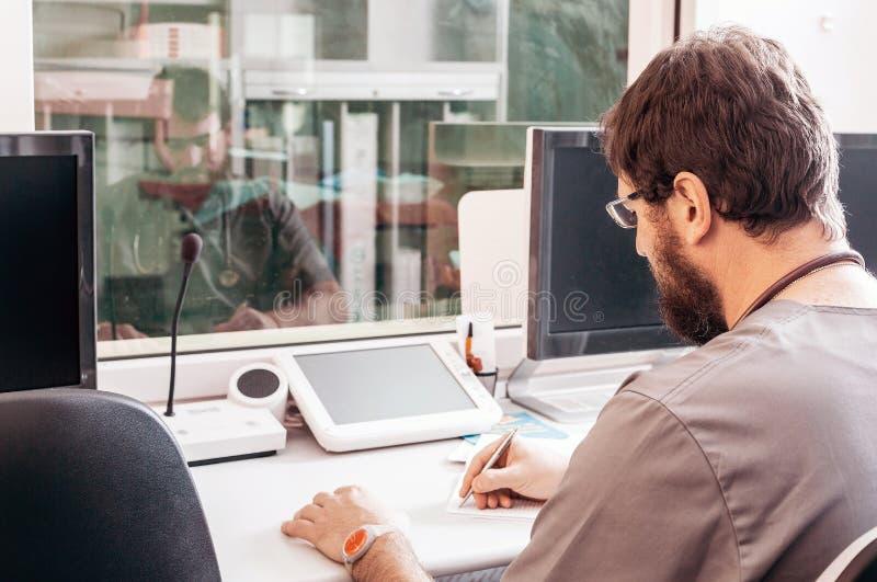 Γιατρός σε μια συνεδρίαση τηβέννων σε έναν πίνακα σε ένα γραφείο νοσοκομείων στοκ φωτογραφία με δικαίωμα ελεύθερης χρήσης