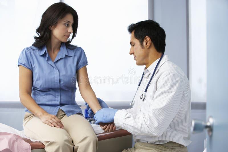 Γιατρός στη χειρουργική επέμβαση που παίρνει το σφυγμό του θηλυκού ασθενή στοκ φωτογραφίες